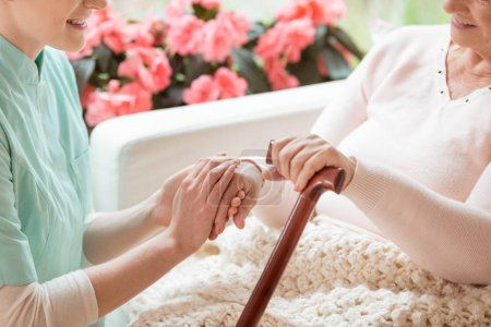 Closeup of a caring volunteer working in a retirement home holding a senior, disabled woman's hand