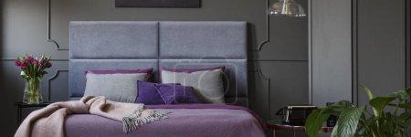 Photo pour Lit double avec bedhead doux, purple draps et oreillers gris debout dans l'intérieur de la chambre noire avec moulure sur le mur - image libre de droit