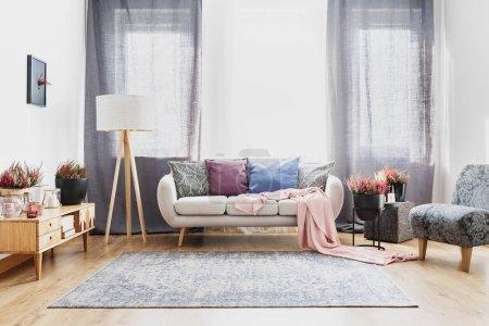 Foto de Cortinas grises detrás de sofá con almohadones coloridos en amplio salón interior con alfombra, la lámpara y brezos - Imagen libre de derechos