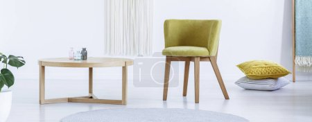 Photo for Panoramic view of a wooden coffee table, yellow chair and pillows on the floor - Royalty Free Image