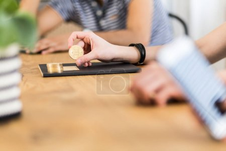 Close-up on person holding gold coin of Bitcoin - symbol of virtual money