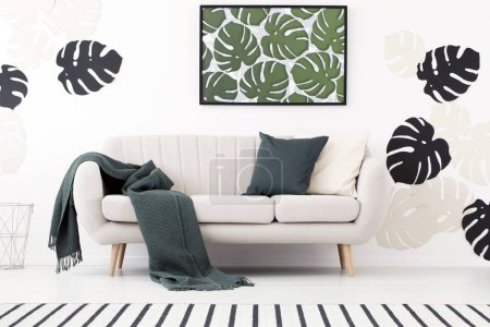Green blanket and cushion on settee in white living room interior with poster of leaves. Real photo