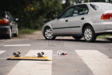 Photo pour Skateboard et chaussure pour enfant sur un passage à niveau piétonnier après un incident de circulation dangereux - image libre de droit