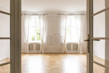 Empty bright living room interior with drapes at windows and wooden floor. Real photo