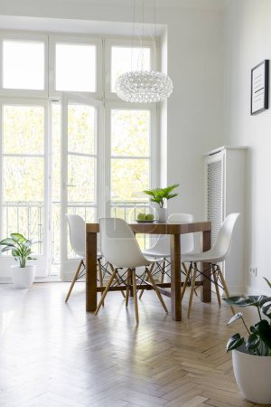 White chairs at table under lamp in bright dining room interior with balcony. Real photo