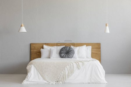Photo for Knit blanket on wooden bed against grey wall in minimal bedroom interior with lamps. Real photo with a place for your nightstand - Royalty Free Image