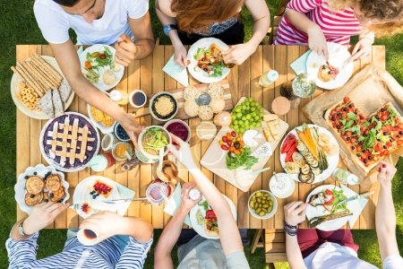 Top view on table with pizza, pastry and fruit. People eating lunch during outdoor party