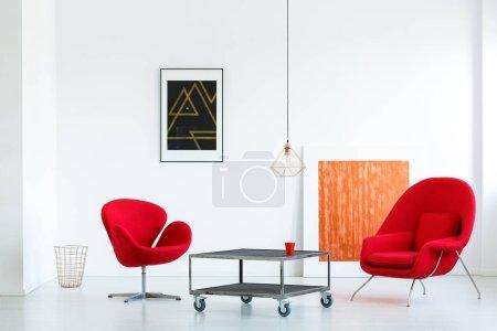 Photo pour Véritable photo de deux fauteuils rouges debout à côté d'une table en métal avec roues dans le salon blanc minimal intérieur avec deux affiches et une lampe - image libre de droit