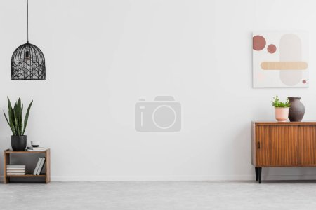 Photo for Retro, wooden cabinet and a painting in an empty living room interior with white walls and copy space place for a sofa. Real photo. - Royalty Free Image