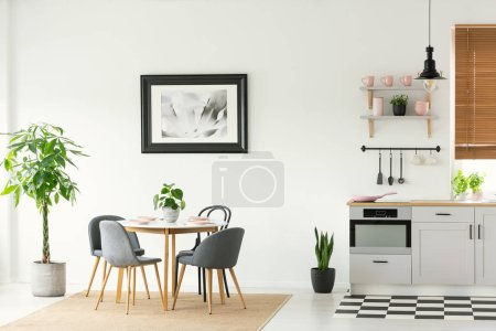 Photo for Framed photo on a white wall in an open space dining room and kitchen interior with modern, wooden furniture and plants - Royalty Free Image