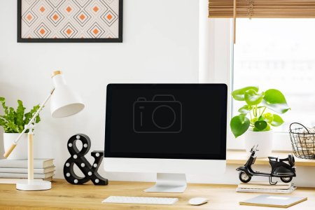 White lamp next to desktop computer on wooden desk in home office interior with plant. Real photo with a place for your graphic