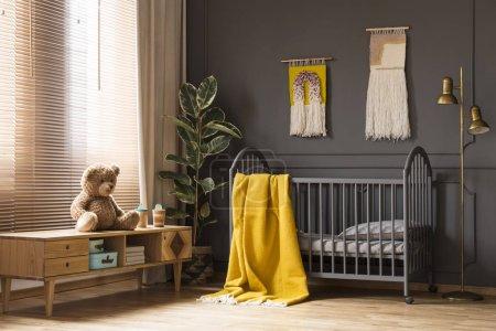 Photo pour Photo réelle d'un lit de bébé avec une note de couverture jaune entre une armoire basse avec un ours en peluche et une lampe à l'intérieur de chambre de bébé - image libre de droit
