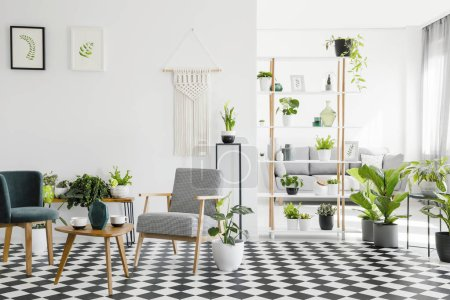 Wooden table between armchairs on checkered floor in living room interior with plants and posters. Real photo