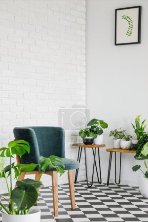 Photo for Green chair on checkered floor in white living room interior with poster and plants. Real photo - Royalty Free Image