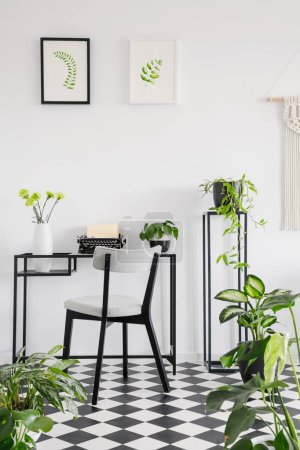 Botanical home office interior with a desk, chair and graphics on the wall. Real photo
