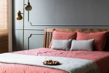 Close-up of grey blanket on pink bed in hotel bedroom interior with gold lamp