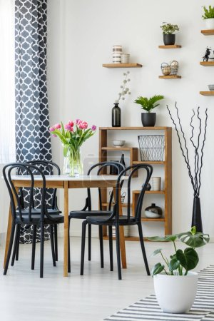 Photo for Industrial dining room interior with a table, black chairs, pink tulips, plants and shelves in the background - Royalty Free Image