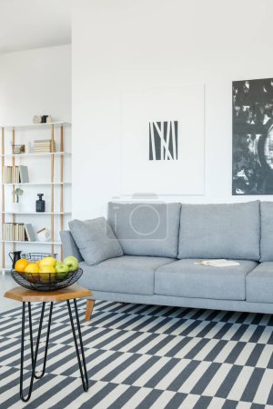 Photo for Grey sofa and table on patterned carpet in bright living room interior with posters. Real photo - Royalty Free Image
