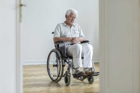 Sad paralyzed senior man in the wheelchair sitting alone at home