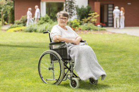 Happy disabled elderly woman in a wheelchair on green grass during a walk in the garden of a retirement home