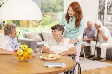 Infirmière amicale soutenant une femme handicapée malade en fauteuil roulant pendant la réunion