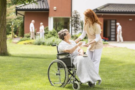 Friendly caregiver giving tea to paralyzed elderly woman in a wheelchair on green grass