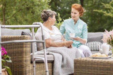 Souriant infirmière amicale donnant du thé à une femme âgée sur la terrasse