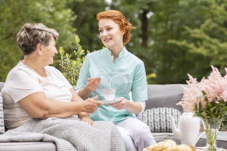 Aide familiale amicale avec thé parlant à une femme âgée dans le jardin