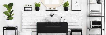 Photo pour Véritable photo de l'intérieur de la salle de bain en noir et blanc avec des plantes vertes fraîches, étagère métallique avec des serviettes et des bougies placées sous le miroir - image libre de droit