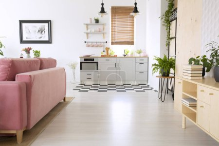 Wooden cupboard and pink sofa in bright flat interior with kitchenette and poster. Real photo