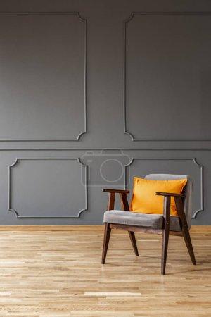 Photo pour Oreiller orange sur fauteuil en bois dans un simple loft gris intérieur avec mur avec moulage. Véritable photo avec une place pour vos meubles - image libre de droit