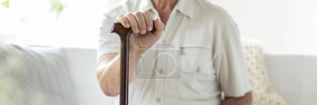 Panorama and close-up of senior person with walking stick. Blurred background