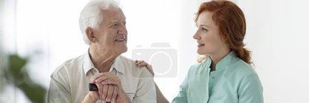 Panorama d'un aîné souriant et d'un soignant amical qui le soutient