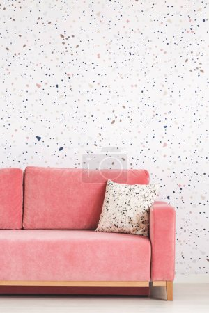 Pillow on pink sofa against patterned wallpaper in bright living room interior. Real photo