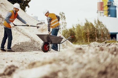 Photo pour Angle bas sur les travailleurs dans des gilets réfléchissants avec des pelles et des brouettes - image libre de droit
