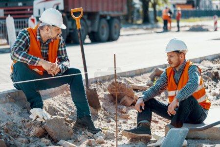 Photo pour Travailleurs en casques blancs et gilets réfléchissants pendant une pause sur les travaux routiers - image libre de droit