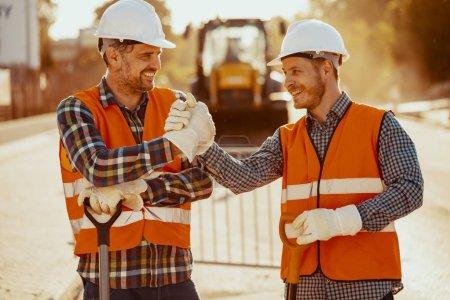 Photo pour Travailleurs souriants en gilets réfléchissants et casques blancs après les travaux routiers - image libre de droit
