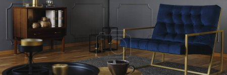 Designer navy blue armchair with golden frame in an elegant, gray living room interior with black and golden decorations. Real photo.