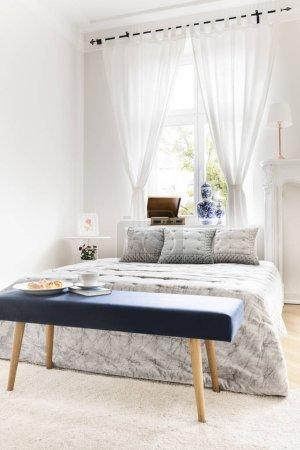 Photo pour Banc bleu marine avec livre et petit déjeuner debout près du lit king-size dans l'intérieur de la chambre blanche avec fenêtre avec rideaux - image libre de droit