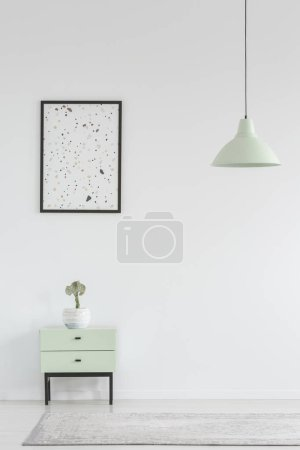 Poster above cabinet with plant in white minimal living room interior with lamp above rug. Real photo with a place for your armchair