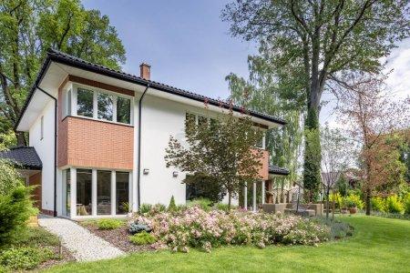 Photo pour Fleurs et arbres devant une maison avec de l'herbe verte au cours de l'été - image libre de droit
