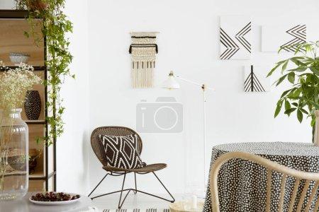 Photo pour Coussin à motifs sur chaise et plante sur tableau blanc boho salon intérieur avec des affiches. Vraie photo - image libre de droit