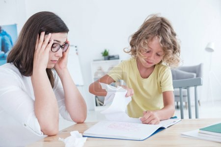 Stressed psychotherapist having a headache during a meeting with a rebellious child with behavioral disorders. The kid is tearing sheets of paper from the notebook.