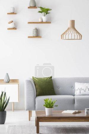 Photo pour Étagères simples avec des vases sur un mur blanc et un mobilier en bois scandinave dans un intérieur de salon lumineux avec un décor gris - image libre de droit