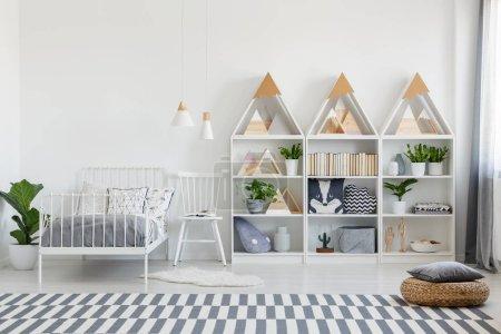 Photo pour Oreillers mignons et livres sur les unités d'étagères en bois et une chaise par un lit jumeau dans un intérieur de chambre eco pour un adolescent - image libre de droit