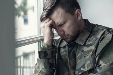 Photo for Depressed and lonely soldier in military uniform with war syndrome - Royalty Free Image