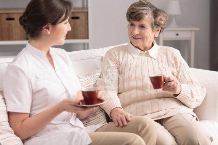 Amical soignant et souriant femme âgée boire du thé pendant la réunion