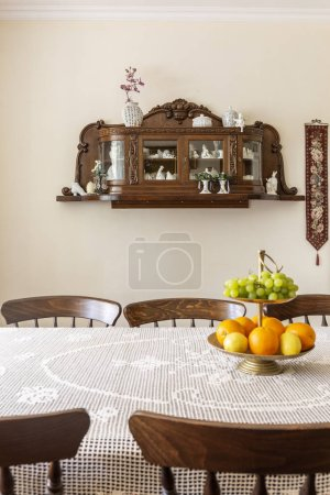 Wooden chairs at table with fruits in white classic dining room interior with shelves. Real photo