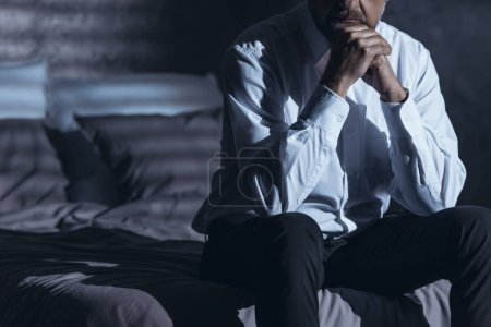 Photo for Close-up of lonely businessman with insomnia problem sitting on the bed in a dark hotel room - Royalty Free Image