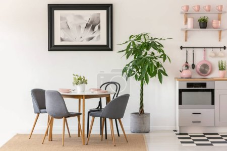 Grey chairs at dining table next to plants in kitchen interior with poster and pink accessories. Real photo